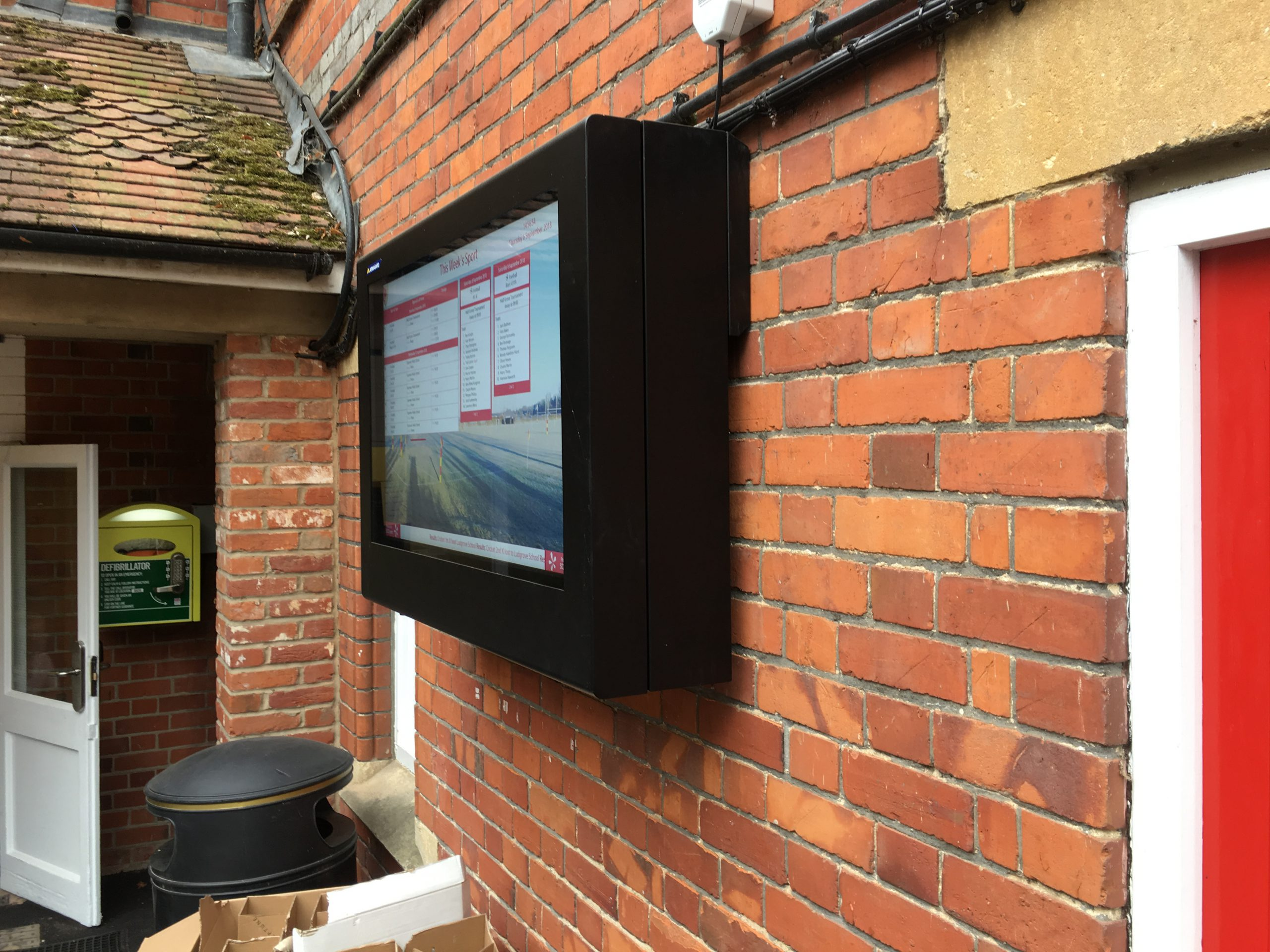 Digital signage with sports fixtures inside a weatherproof enclosure at Moulsford School