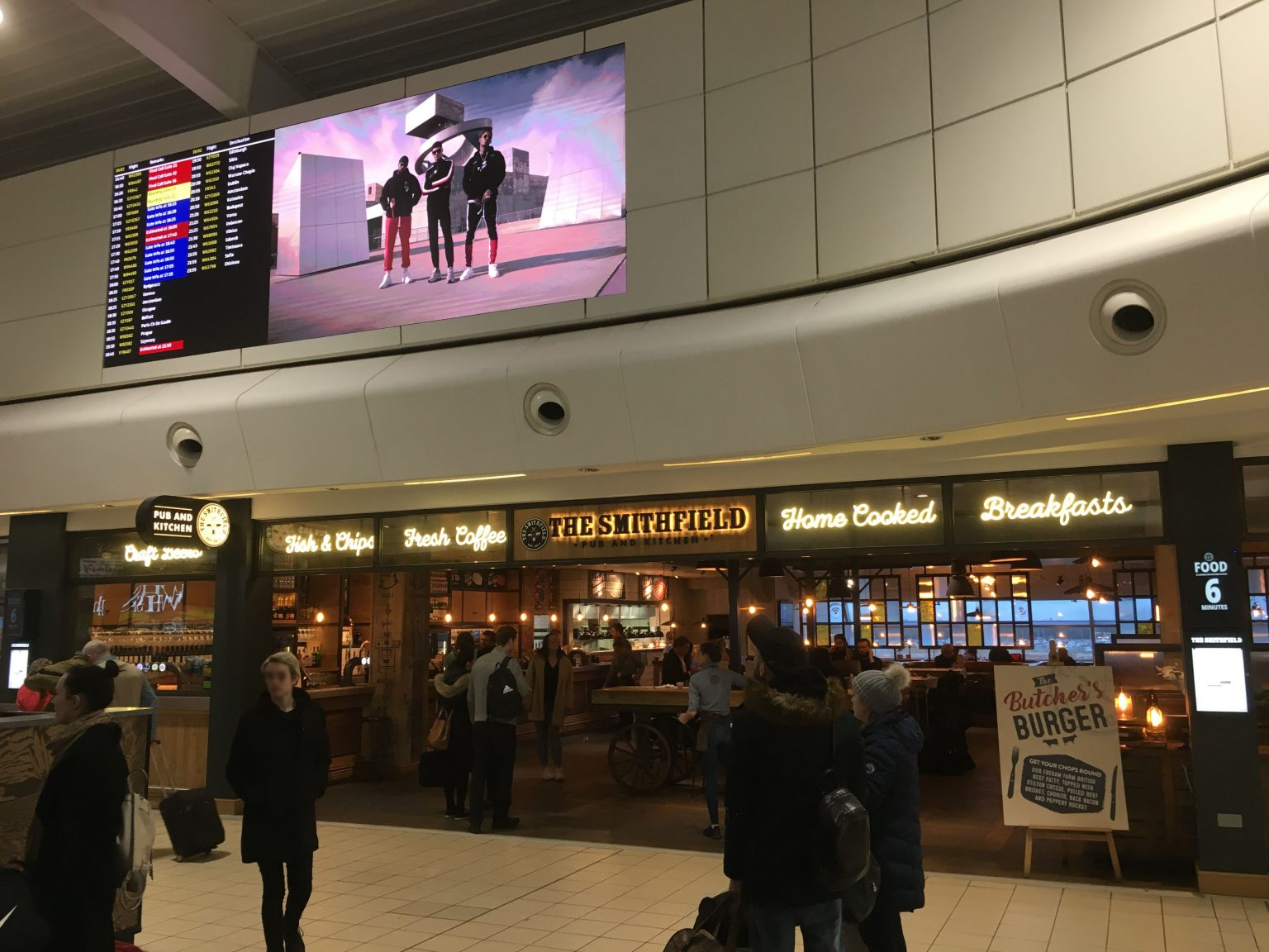 LED wall with flight information and advertising at London Luton Airport