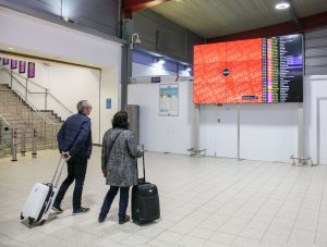 Passengers checking video wall with advertising and flight information