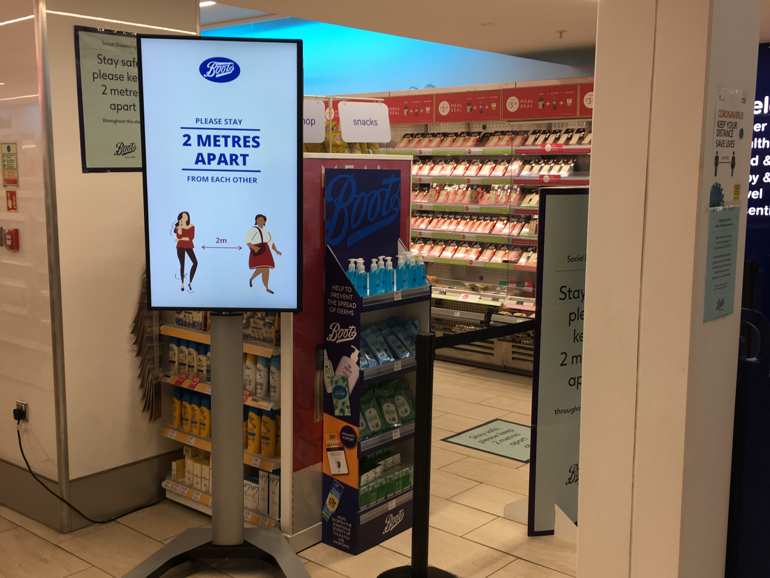 Digital sigange with COVID-19 guidelines at Boots at London Luton Airport