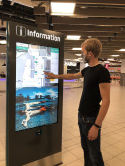 Young men wearing a face mask while interacting with the wayfinding totem at London Luton Airport