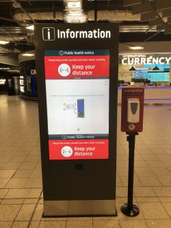 London Luton Airport Wayfinding Information Totem with hand sanitizer stand next to it